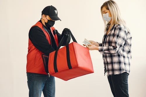Young blond woman in checkered shirt and medical mask paying cash to young delivery man in protective mask and gloves during safety food delivery in studio