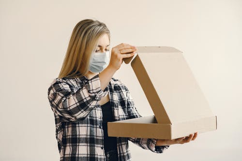 Young woman in medical mask opening pizza box