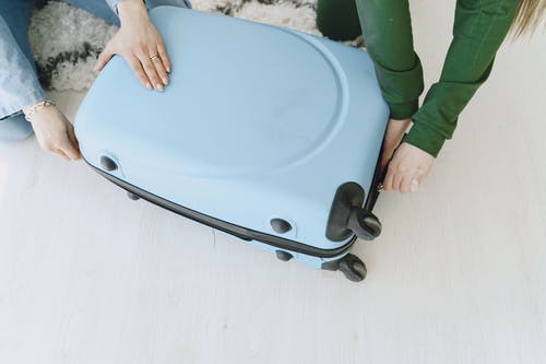 Unrecognizable female friends in casual clothes sitting on floor with fluffy carpet and opening suitcase together while preparing for journey and adventure