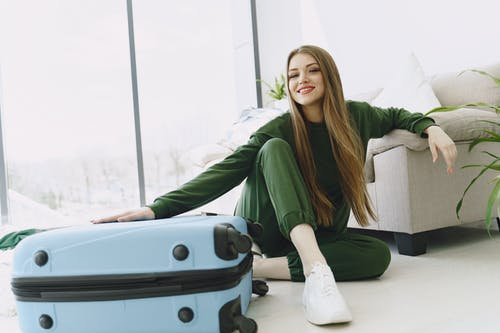 Happy young woman preparing for travelling in modern apartment