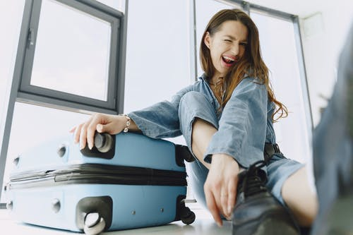 Low angle of young exited female traveler with suitcase in stylish outfit having fun before flight