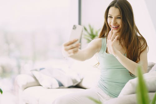 Cheerful young woman using smartphone during video call