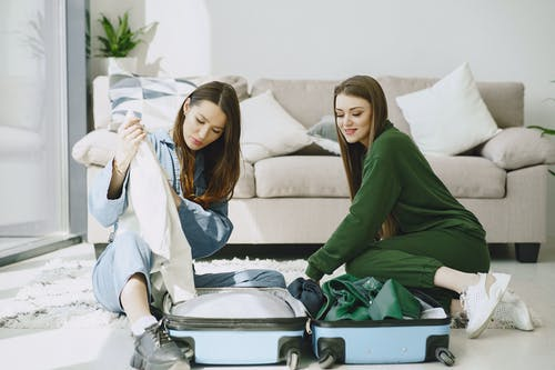 Optimistic young female travelers in trendy outfits sitting on floor against comfortable sofa and unpacking suitcase in modern hotel room