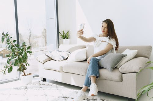 Positive young female doing selfie on smartphone while sitting on sofa