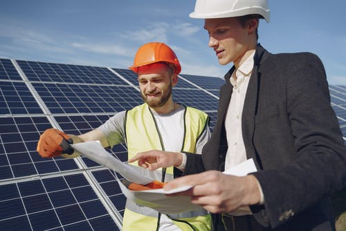 Concentrated men working together near solar panels