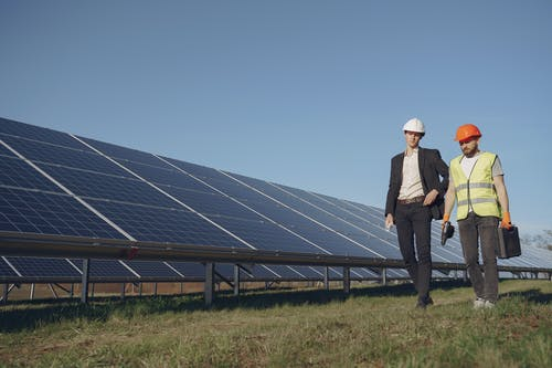 Concentrated male coworkers in hardhats working against solar panels