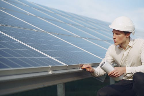 Serious young man working near solar panels