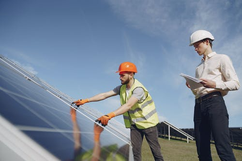 Technician and manager checking equipment for solar energy station