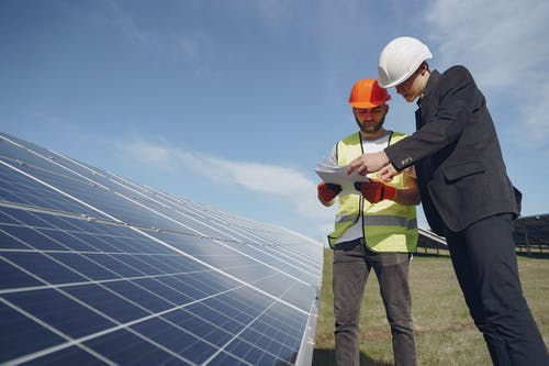 Low angle of young inspector and foreman in hardhats checking documentation against modern solar panels in field