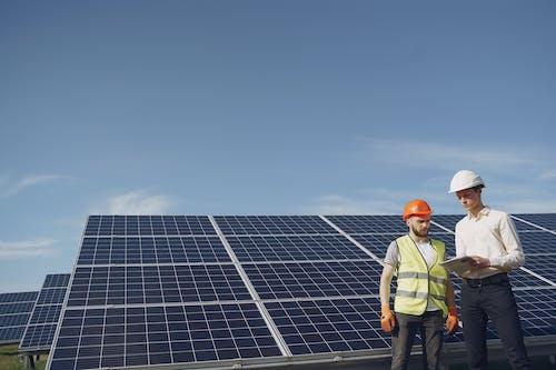 Focused men working against solar panels