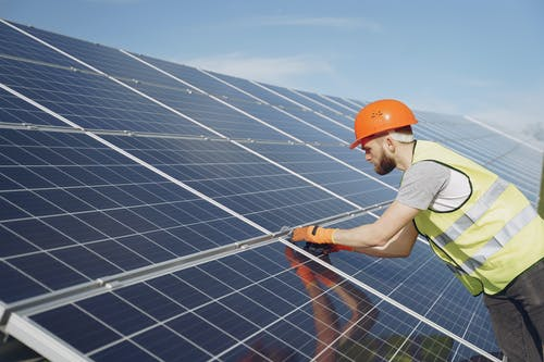 Side view of focused young man in uniform and hardhat checking setup of solar panels