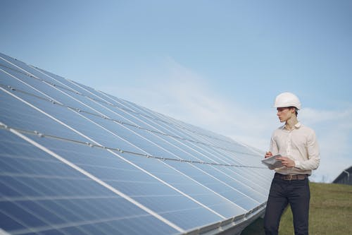 Young man inspecting solar panel station