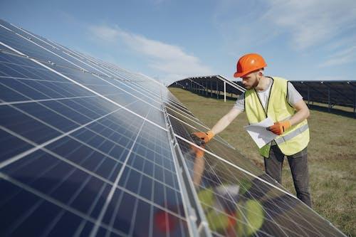Male supervisor inspecting solar panels on field under blue sky