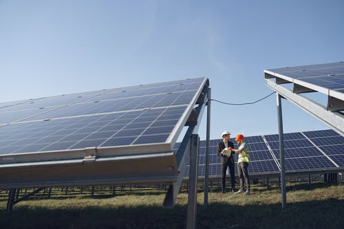 Supervisor in hardhat and formal wear discussing project with workman in uniform while standing with papers near modern solar panels under blue sky