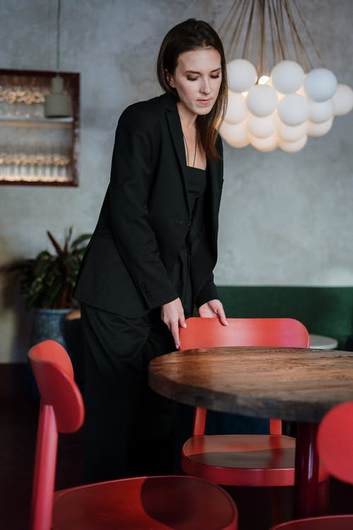 Woman in Black Blazer Standing Beside Brown Wooden Table