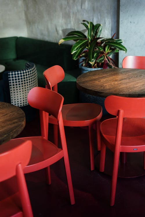 Red Plastic Chair Near Brown Wooden Round Table
