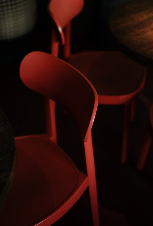 Red Plastic Chair Near Black Textile