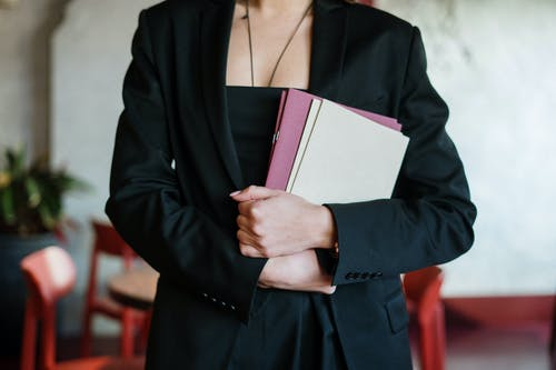 Woman in Black Blazer Holding Pink and White Book