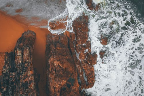 Breathtaking drone view of foamy ocean waves crashing near rough stony formations  on sandy beach
