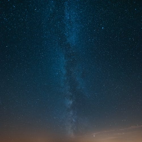 From below of bright night sky with shining stars and Milky Way galaxy