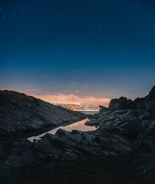 Black Rocky Mountain Near Body of Water during Night Time