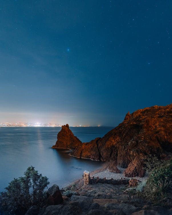 Spectacular landscape of rocky hill and formations in peaceful sea under cloudless starry night sky