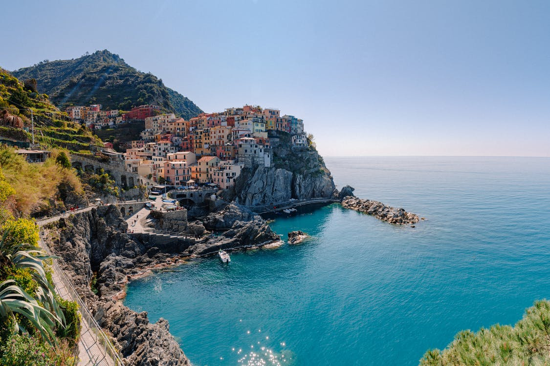 Breathtaking scenery of historic colorful buildings of famous coastal Manarola town located on stony hill in front of turquoise sea on sunny day