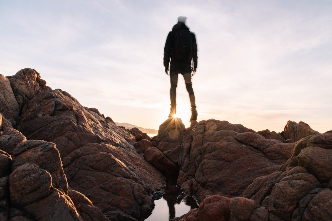 Full body unrecognizable tourist in black jacket with backpack standing on rocky shore and admiring sunrise