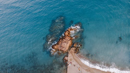 Aerial View of Brown Rock Formation on Body of Water