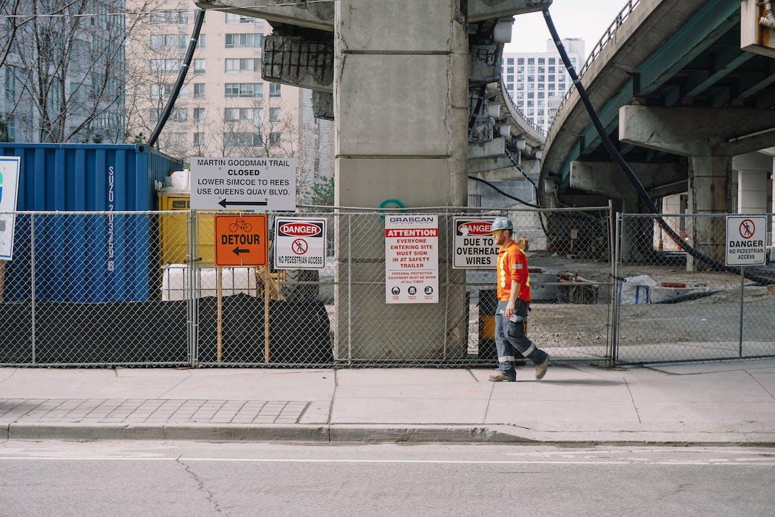 Full body side view of adult male worker in orange uniform and grey helmet walking under big bridge along chain link fence on street in daylight