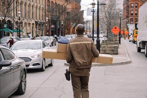 Man in Brown Coat Carrying Brown Cardboard Box