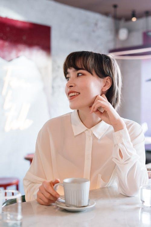Woman in White Long Sleeve Shirt Holding White Ceramic Mug