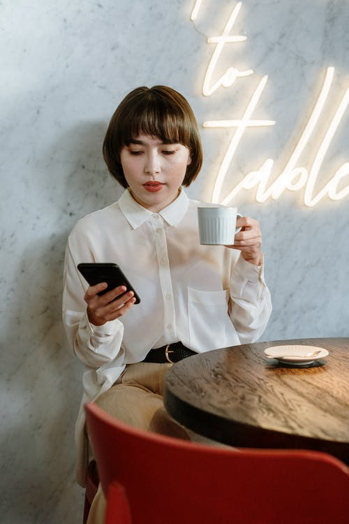 Boy in White Dress Shirt Holding Black Smartphone