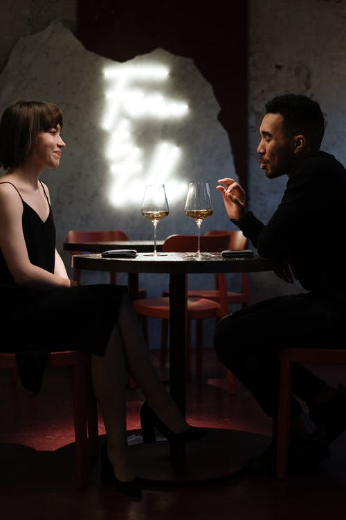 Man and Woman Sitting on Chair in Front of Table