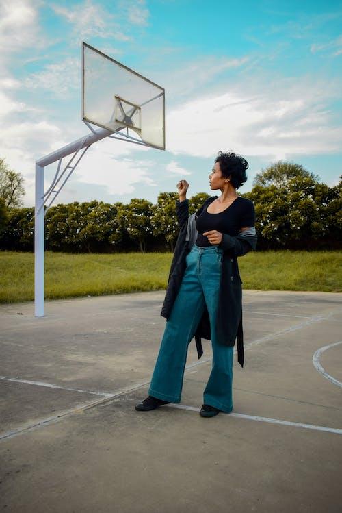 Full body brunette in denim and coat standing on basketball sports ground in suburbs