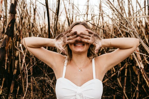 Happy anonymous lady in pendant standing with raised dirty hands hiding face behind overgrown dry stems in field in countryside