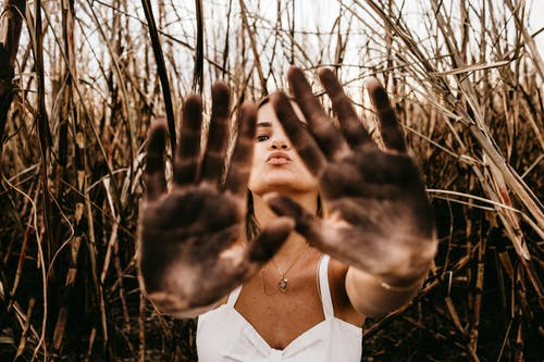 Woman giving five with dirty palms of hands in field