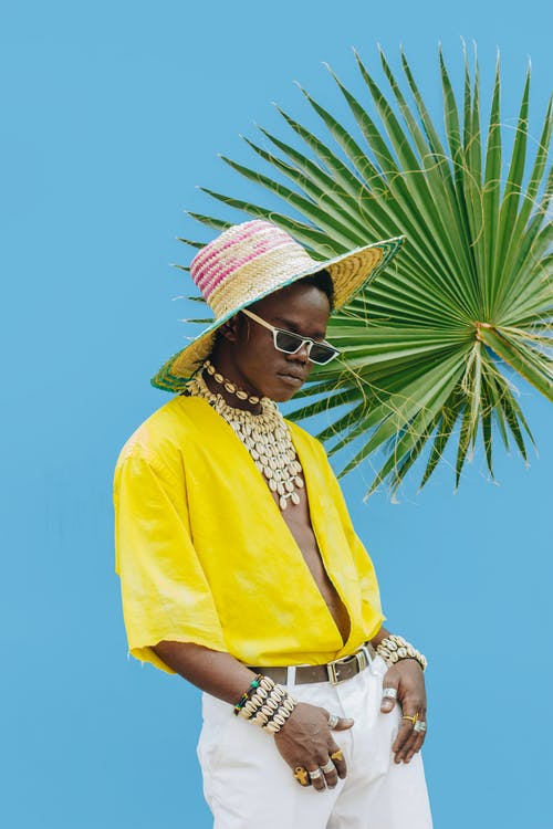 Frau In Der Gelben Strickjacke, Die Braunen Sonnenhut Und Sonnenbrille Trägt