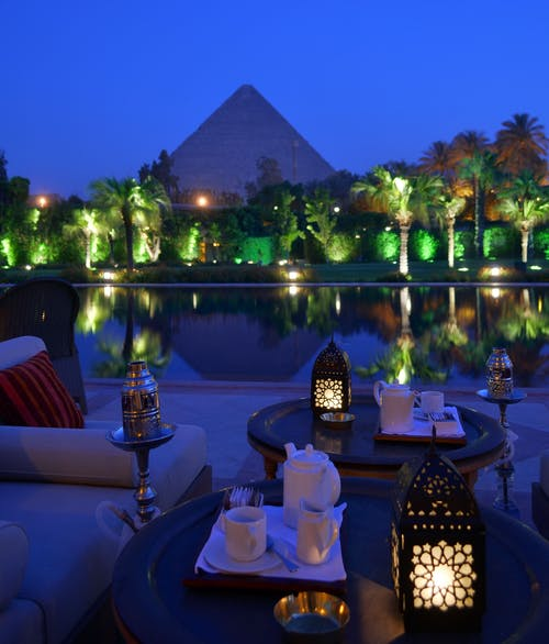 From above of cafe with dishware and ornamental lanterns on round tables near sofa and pond reflecting trees and old pyramid under blue sky illuminated by artificial lights