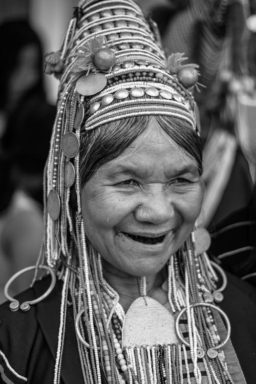 Content elderly ethnic woman in traditional headwear