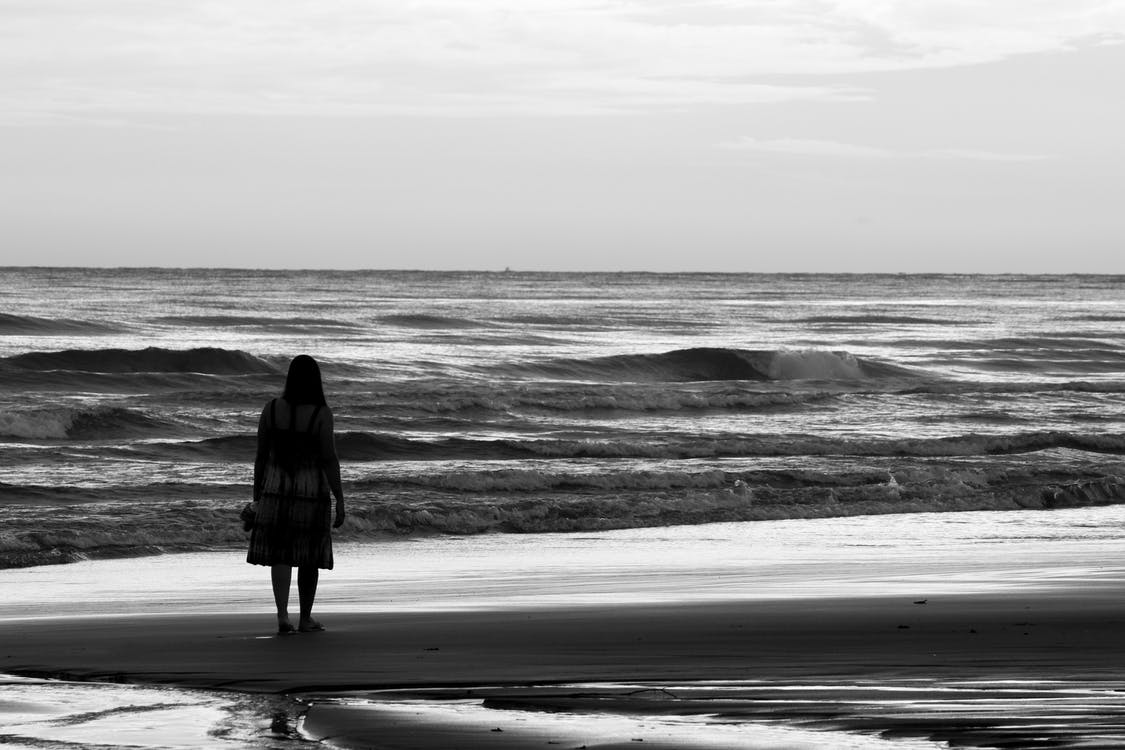 Black and white back view of unrecognizable alone female silhouette admiring stormy ocean while standing on sandy coast under cloudy sky with horizon line