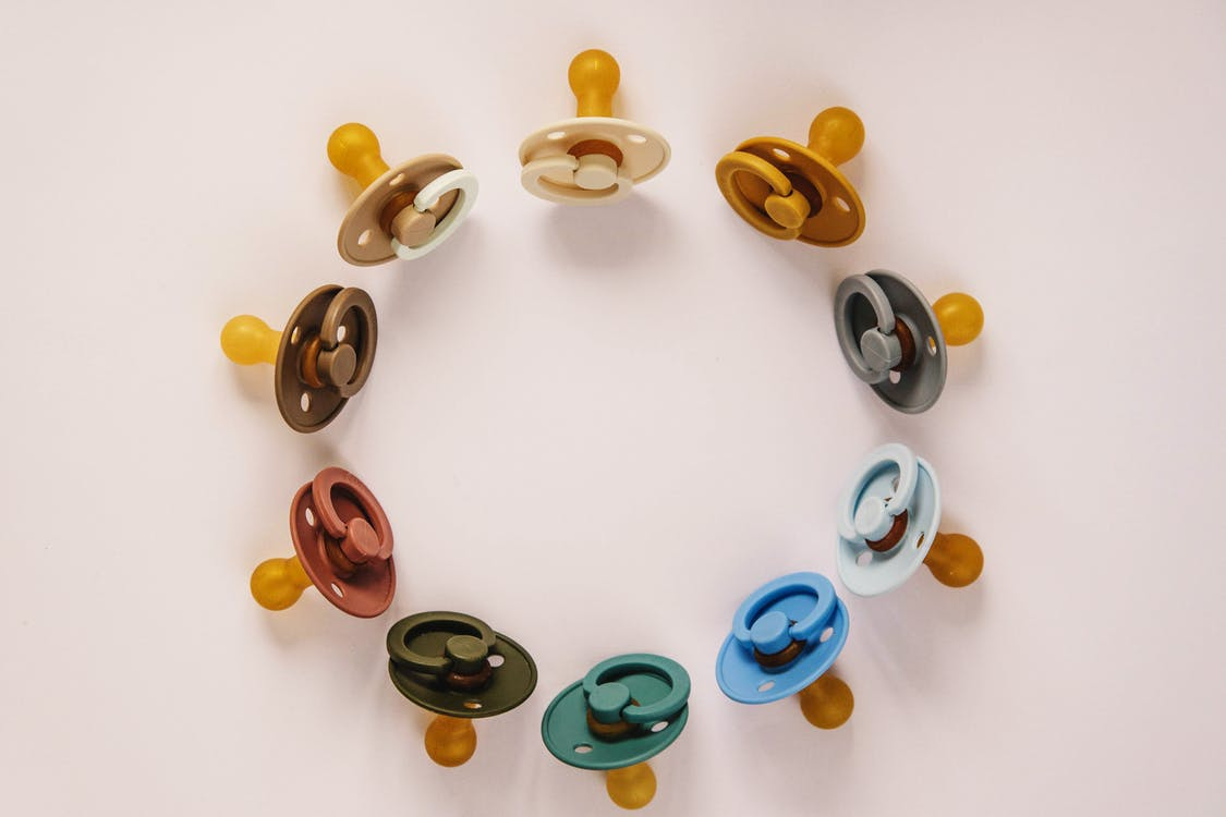 Set of multicolored baby pacifiers on table