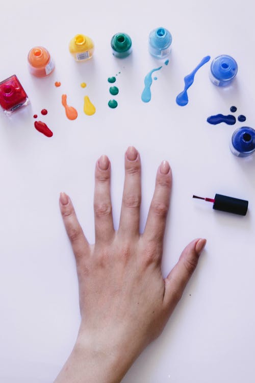 From above of crop unrecognizable female demonstrating hand with manicure and choosing bright color from set of rainbow spectrum nail varnishes