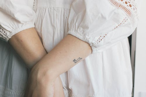 Crop woman in white linen dress with embroidery