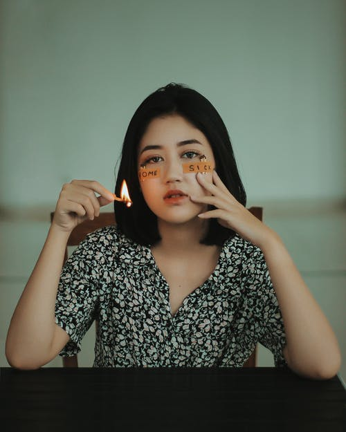 Melancholische Asiatische Frau Mit Brennendem Streichholz, Das Während Covid Nach Hause Fehlt