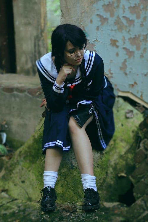 Pondering ethnic teenager in school uniform sitting on mossy stone