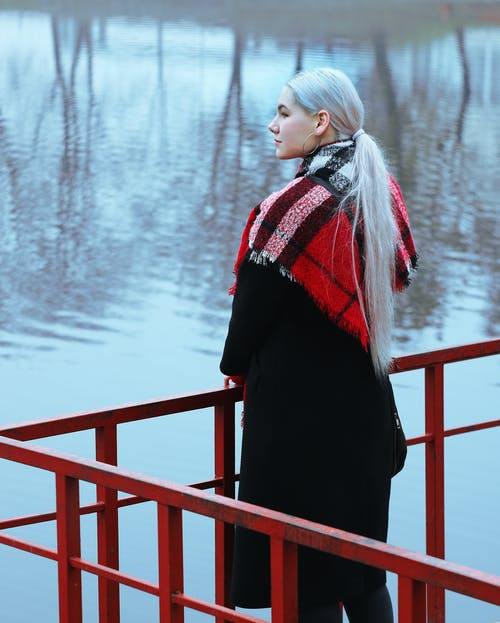 Back view of young trendy female in bright scarf contemplating pond with rippled water reflecting trees near metal fence and looking away