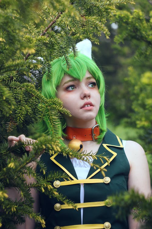 Pondering female teenager in costume and colorful wig with evil horns looking away while standing near coniferous tree in daytime