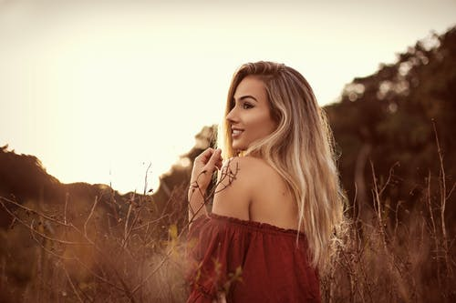 Smiling elegant blond woman in field under sky