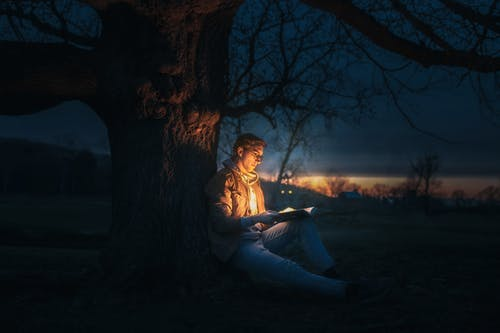 Man Sitting Under A Tree Reading A Book during Night Time
